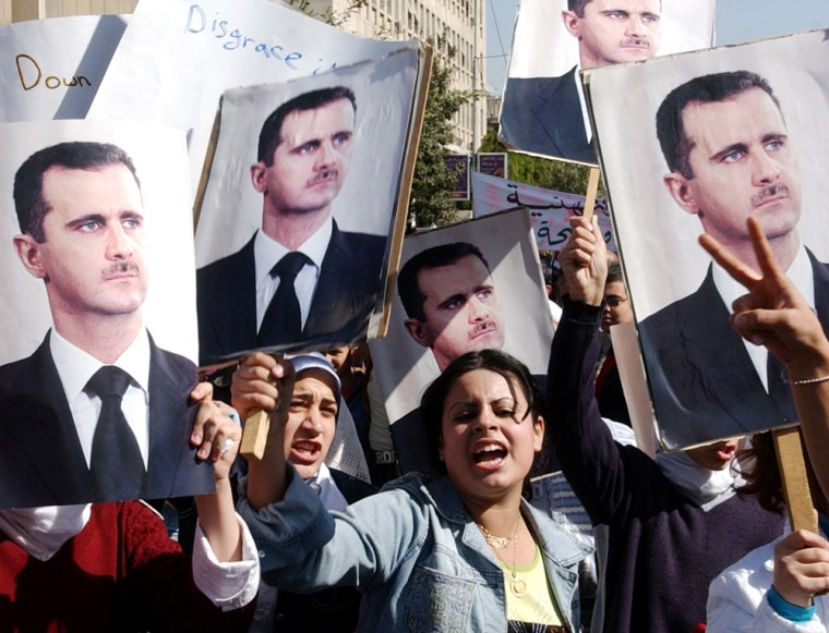 Syrian women hold posters showing President Bashar Assad as they demonstrate in Damascus on Monday, to protest against the U.N. report on the assassination of former Lebanese Prime Minister Rafiq Hariri that implicated Syrian and Lebanese officials.
