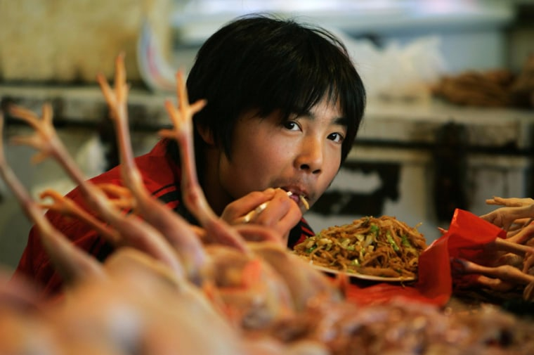 A young Chinese man eats next to freshly killed chickens at his chicken stall in a Beijing market on Oct. 28.