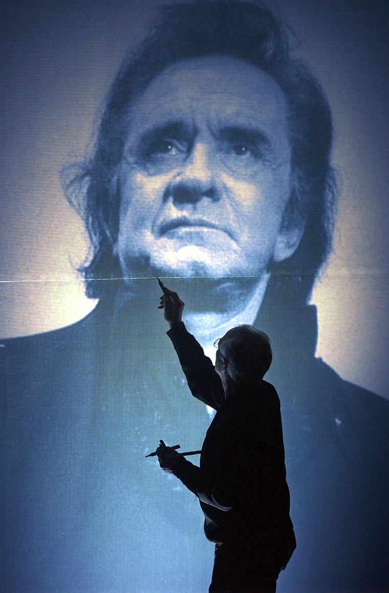 An artist touches up a background portrait of Johnny Cash on stage before the Johnny Cash Memorial Tribute last year. Cash ranked No. 10 on Forbes' list of top-earning dead celebrities.