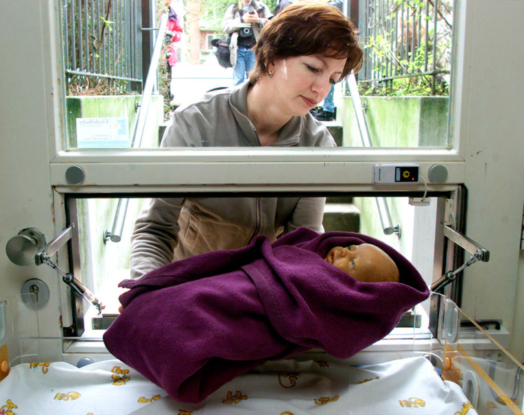 Heidi Rosenfeld, leader of the baby drop project Findelkind, uses a doll to showhowababy drop station in Hamburg,Germany, works.Women can put anunwanted newbornthrough a small opening in a flap door without being registered or recognized.