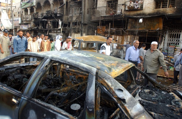 Residents surveyburned cars Tuesday,a day after a powerful roadside bomb exploded in Basra, Iraq.