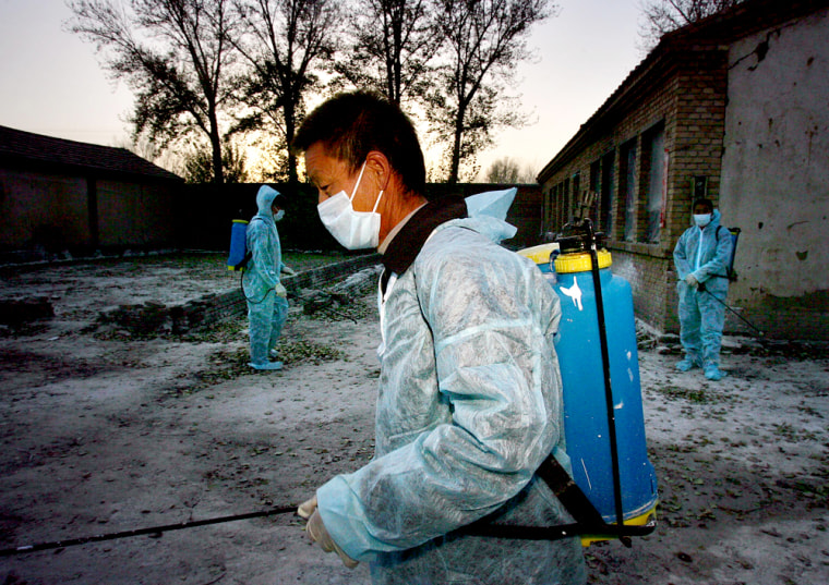 Officials in protective suits spray disinfectant outside a farm in the northern grasslands of the Inner Mongolia region that suffered the first of three outbreaks of bird flu reported over the past month in China.