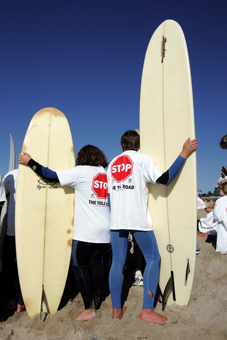 Surfers prepare to paddle out to sea on Oct. 29 to protest a toll road project in San Clemente, Calif.