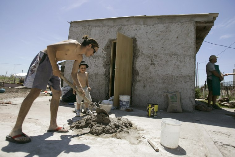 Leonardo Gonzalez, 21, joined by his son Julio, 4, works on his house in a slum near Friday's summit of American leadersin Mar del Plata, Argentina.
