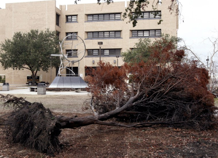 An uprooted tree lies in front of a building on the campus of Xavier University in New Orleans.