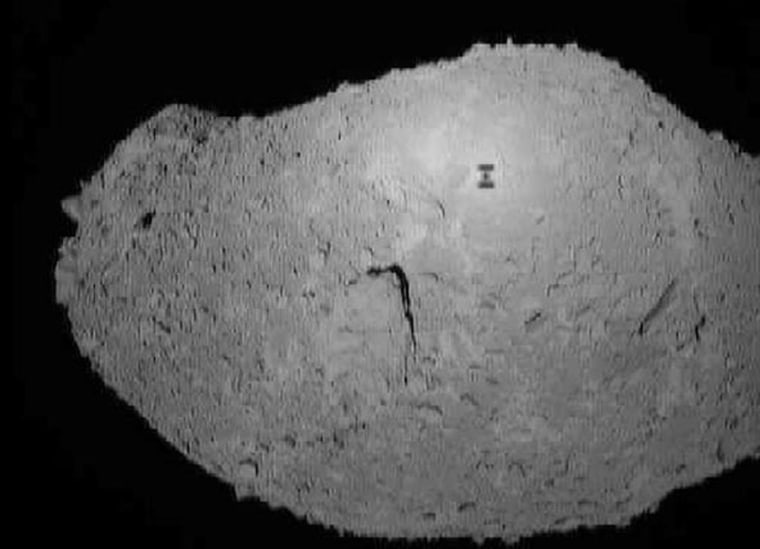 The Japanese Hayabusa probe lined itself up precisely between the sun and asteroid Itokawa, so that Hayabusa could take a picture of its own shadow on the asteroid's surface. The shadow is the dark, I-shaped mark seen in this image.