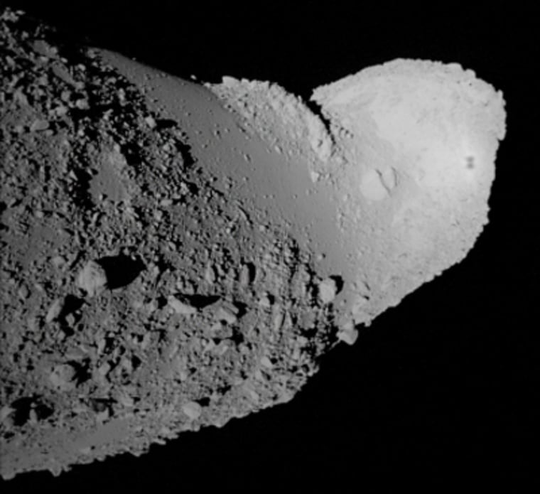 A picture taken by the Hayabusa probe during its close approach shows the tip of the asteroid Itokawa. Hayabusa's shadow can be seen near the asteroid's edge as an I-shaped mark.