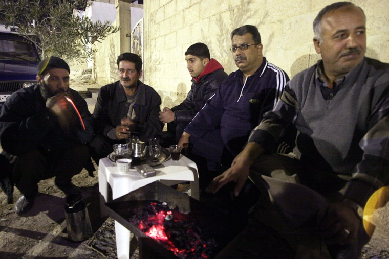 Zoheir Najjar, Abed el-Momani, Mohammed el-Merri, Malek Mreish and Ayman Tawalby, chat, late Saturday, outside their home in the hilly desert city of Zarqa, 15 miles northeast of Amman.