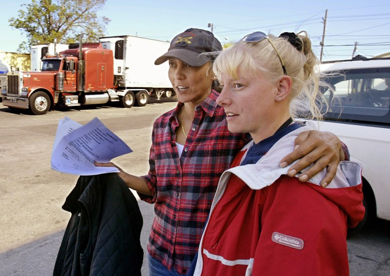 Lily Duke, founder, creator and manager of a large food, water and ice distribution center on Newton Street in New Orleans puts her arm around the shoulders of Angela Cook, a friend and firefighter from Blanchard, Mich.
