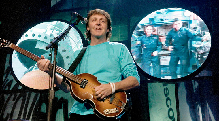 Former Beatle McCartney performs as cosmonaut Tokarev and astronaut McArthur are projected on screen in Anaheim