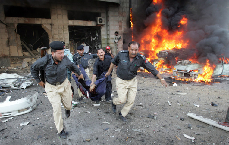 Pakistani police officials carry a body from a building after a bomb blast in Karachi