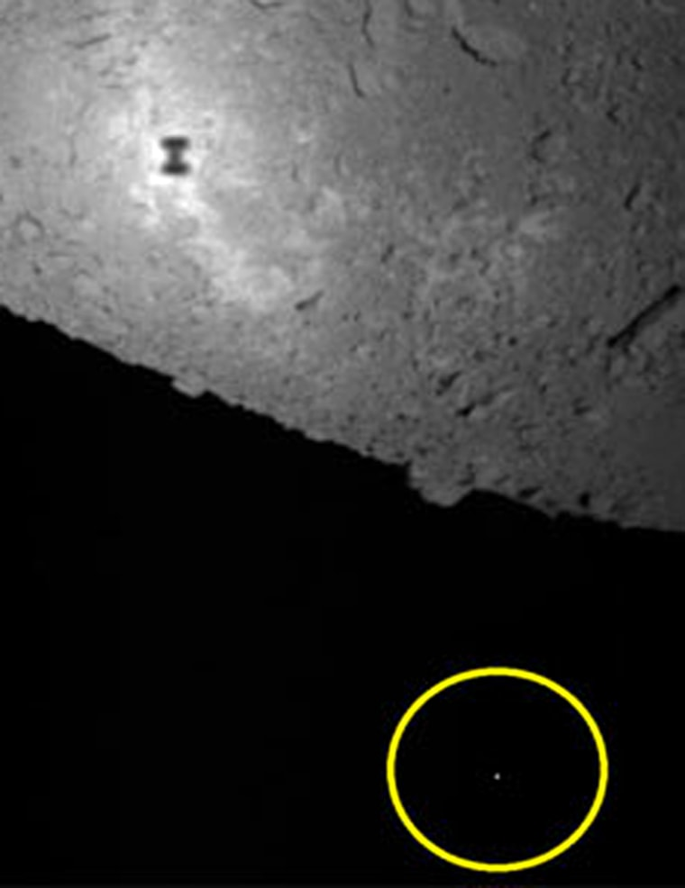 In this photo, taken by the Hayabusa mothership, the object within the yellow circle is thought to be the MINERVA mini-robot, floating in space.Hayabusa's shadow can be seen on the surface of asteroid Itokawa, toward the top of the frame.