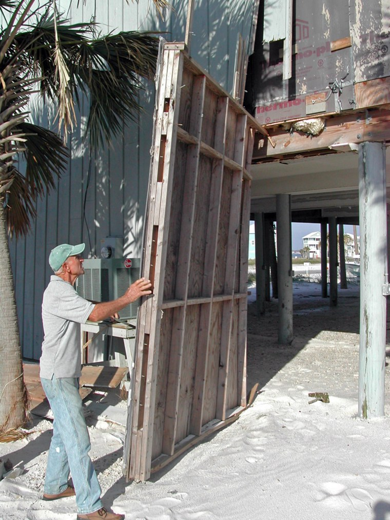 Gene Hudkins works to repair his beach house at Navarre Beach on Santa Rosa Island, Fla., in November.The bottom floor, where he had his workshop, has beenwrecked three times since he built the house in 1994.