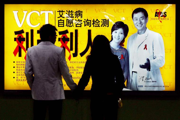 A Chinese couple wait at a subway station in front of an AIDS awareness campaign poster in Beijing