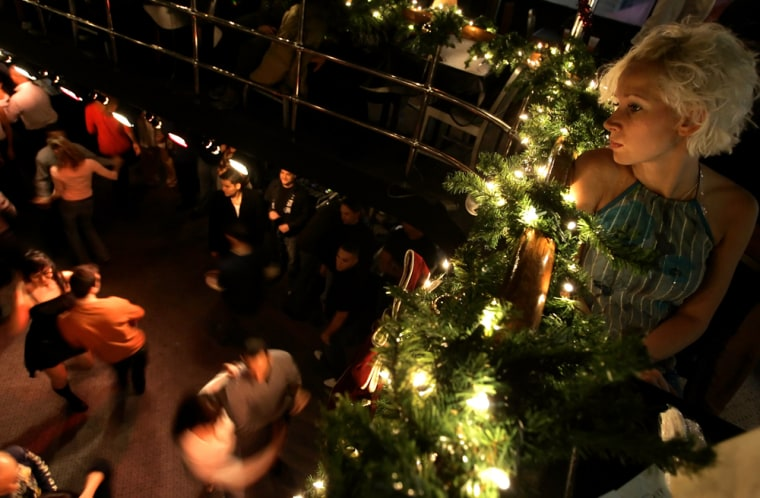 Lisa Westberg, of Sweden, watches dancers aboard a sightseeing boat as it cruises the Hudson River in New York, Thursday, night Nov. 24, 2005.