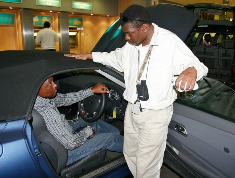 Salesman Zwelie Ncube tries to convince Floyd Tshabalala, 42, to buy the Chrysler Crossfire at the Soweto Motor Show.