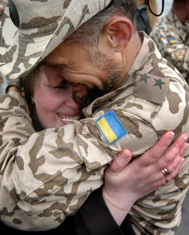 A Ukrainian soldier embraces his wife after returning from Iraq outside theUkrainian capital of Kiev in May. Key U.S. allies Bulgaria and Ukraine will begin withdrawing their troops by mid-December.