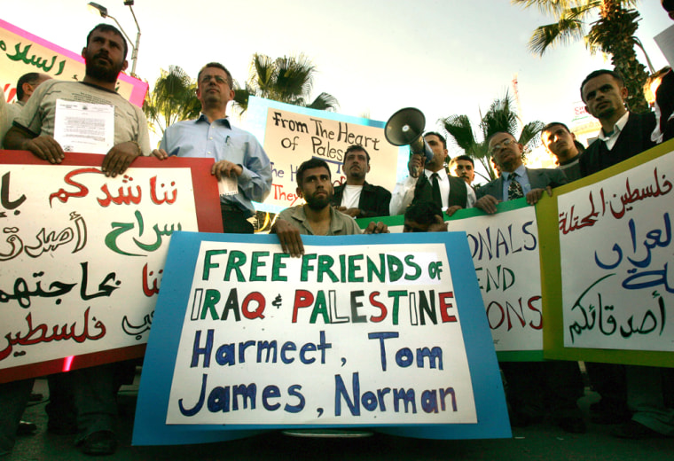 Palestinians hold banners during a demonstration n the West Bank town of Ramallah onThursday, calling for the release of four foreigners kidnapped in Iraq.