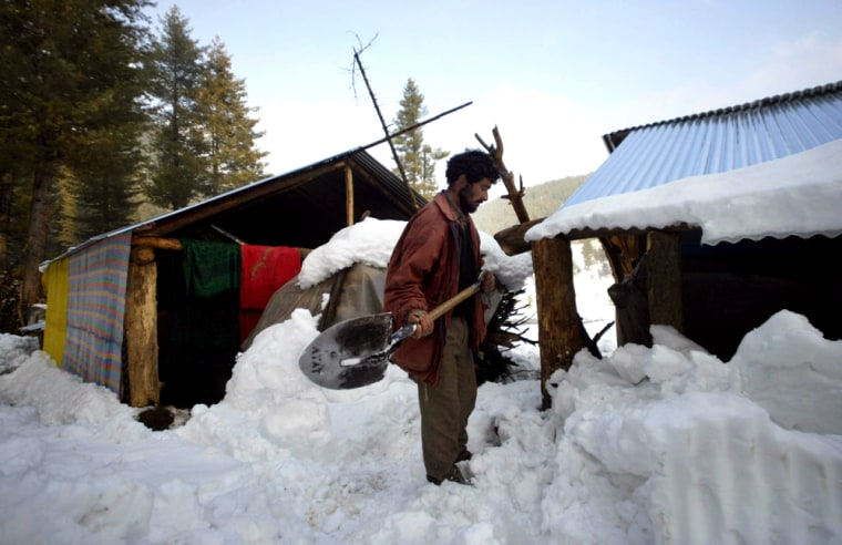 Uness Khan, a earthquake survivor clears snow from his temporary shelter in Drangyari, north of Srinagar, India, on Thursday. Worsening weather has severely hampered aid efforts in earthquake-ravaged northern Pakistan.