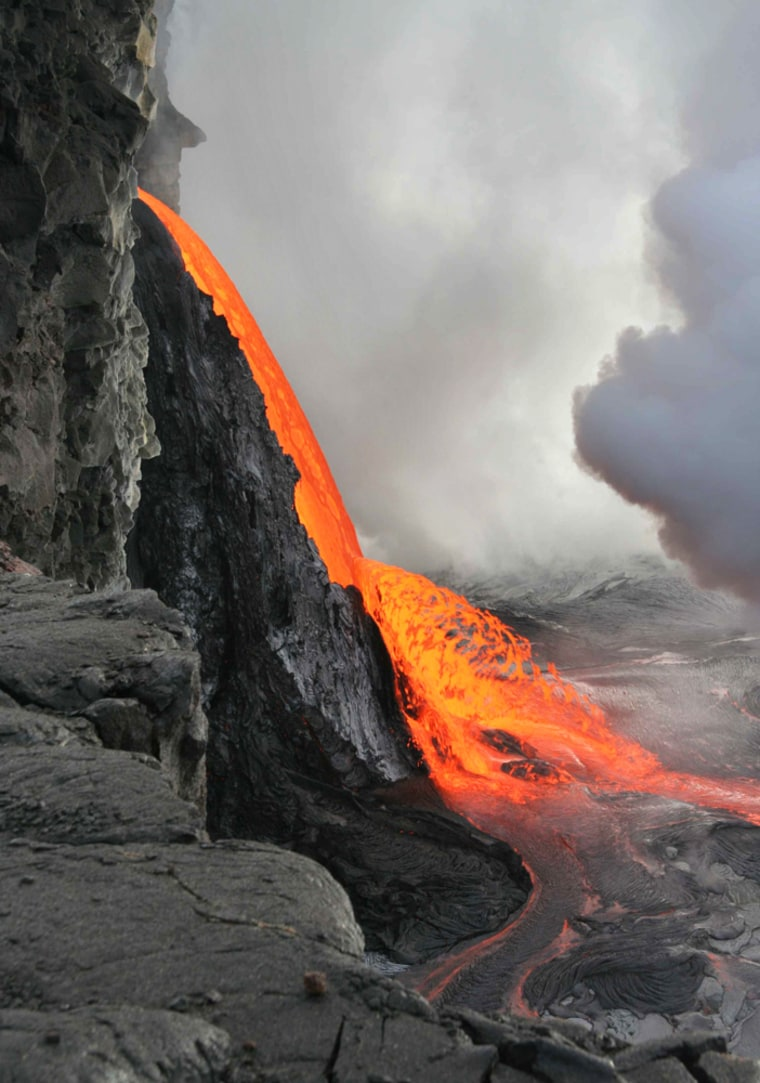 Coastline at Hawaii Volcanoes National Park falls into the ocean Monday, exposing the cliffside and a stream of lava shooting from the cliff face. The glowing lava has since formed a ramp of new land.