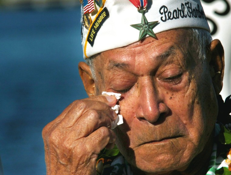 Herb Weatherwax cries during a sunrise ceremony in front of the Arizona Memorial in Pearl Harbor