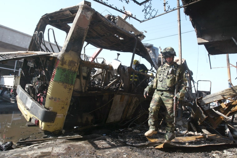 An Iraqi soldier inspects the site ofThursday's suicide attack at a Baghdad bus station.