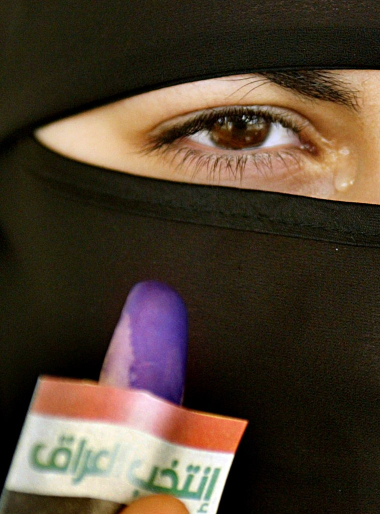 A veiled Iraqi woman reacts as she shows off her finger stained with blue ink at a polling station in Amman