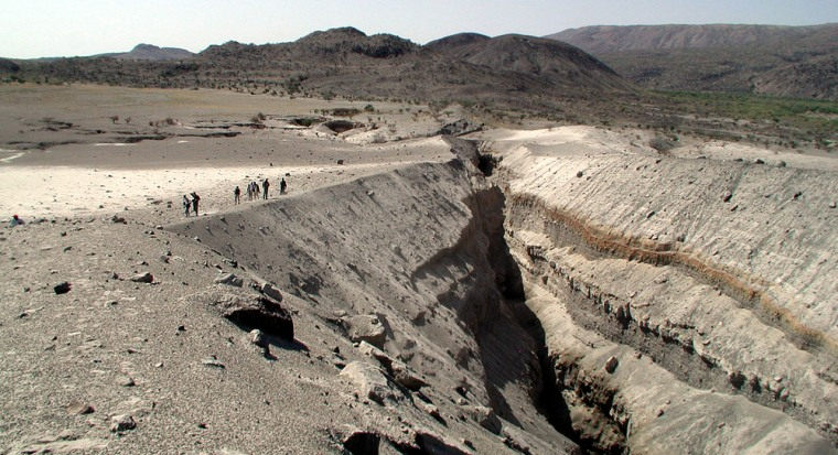 Researchers stand on the brink of a steep slope leading down to a fissure in the Ethiopian desert, in a barren region called Boina or Dabbahu.