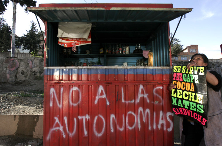 """Aymara Indian street vendor Juana Ilasanca sets up her shop in the outskirts of La Paz, Bolivia.Calls for independence are becoming a major election issue as the country heads to the polls this Dec. 18. The graffitti reads """"No to the Autonomy."""""""