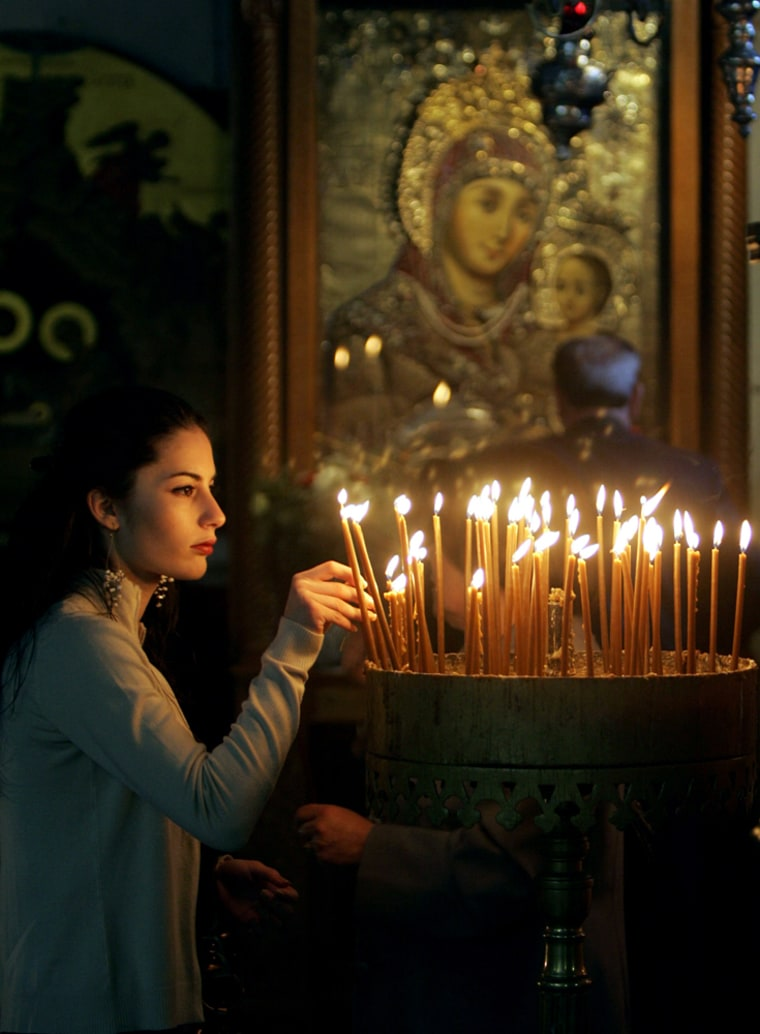 Christian woman lights candles during th