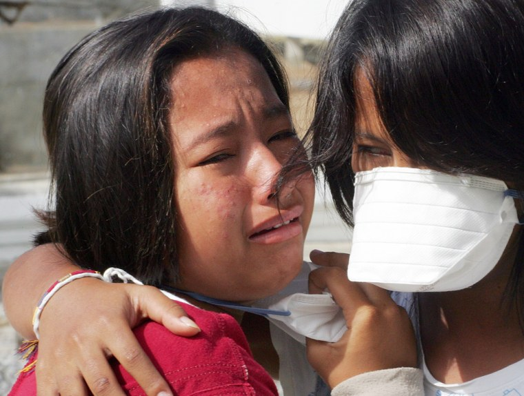 Thai girl cries after seeing the remains of her father's body at a morgue in Phang Nga province