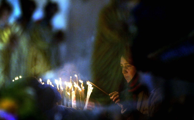 Christian pilgrim lights candle as she is reflected in an icon inside Nativity Church in Bethlehem