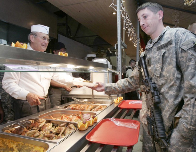 U.S. Secretary of Defense Donald H. Rumsfeld serves Christmas dinner to soldiers in Mosul, Iraq, on Saturday. Rumsfeld is in Iraq to thank the troops for their service.