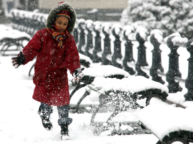 A girl plays in the snow near the Brandenburg Gate in Berlin