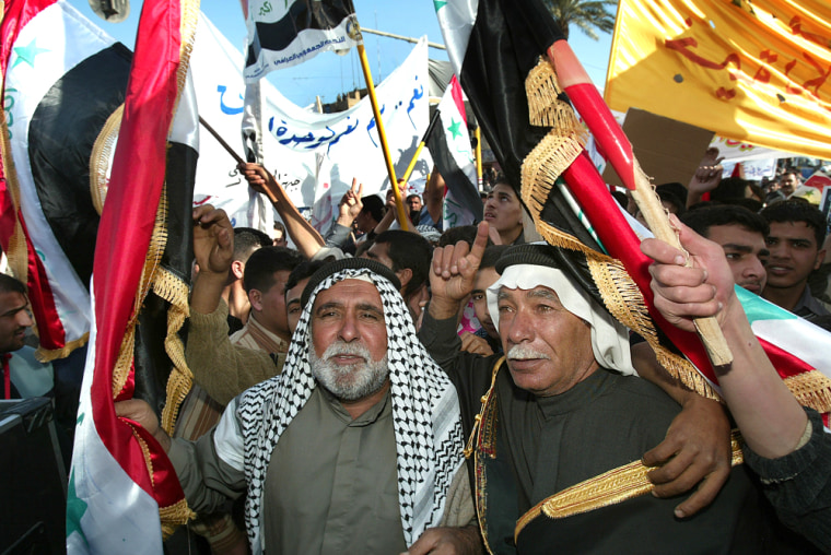 Demonstrators, some waving the national flag, take part in a rally Tuesday in Baghdad, Iraq. More than 10,000 people backing Sunni Arab and secular Shiite politicians marched through Baghdad on Tuesday in support of a national unity government.
