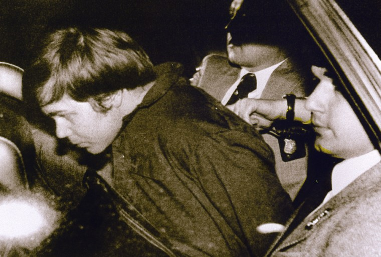 John Hinckley Jr. (L) escorted by police in Washington, DC, on March 30, 1981 after he shot and seriously wounded President Ronald Reagan.