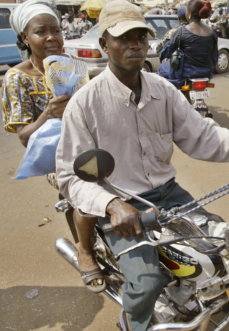 A woman is transported by a male motorcycle driver in Lagos, Nigeria in December. A new Islamic law barring male motorcycle-taxi drivers from transporting female passengers in parts of Nigeria has stranded many women on the streets.
