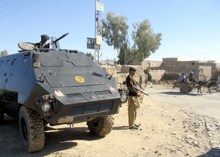 Pakistani paramilitary soldiers with an armoured personal carrier guard a street in Miranshah