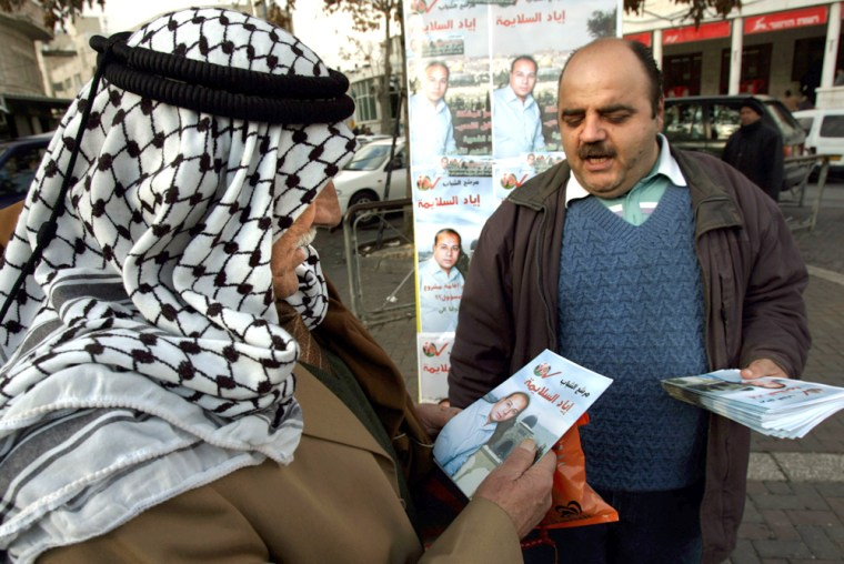 A Palestinian hands out an election campaign flyer to a prospective voter on Monday in Jerusulem, where Israel had threatened to prevent Palestinians from voting.
