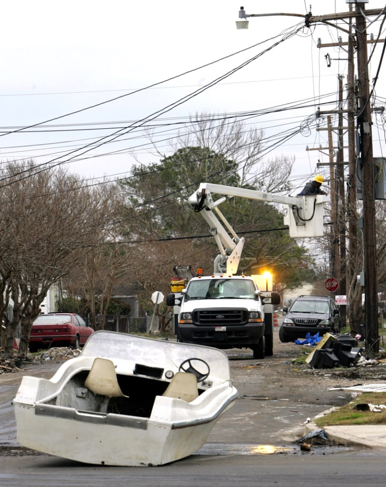 A boat sits in the street of New Orleans as a utility worker repairs lines Tuesday.