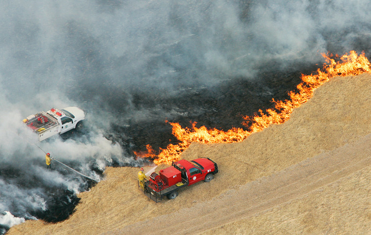Firefighters battle a grass fire near Seminole, Okla. on Jan. 4. Cattle ranchers in Oklahoma and Texas are concerned about the fires, and are holding off on expanding their herds during a time of year they would normally be doing just that.