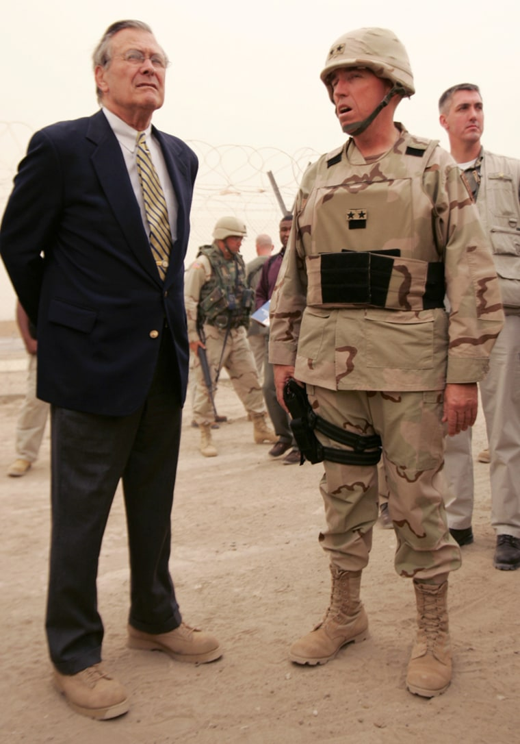 Defense Secretary Donald H. Rumsfeld, left, tours the Abu Ghraib prison with Maj. Gen. Geoffrey Miller, right, in May 2004.