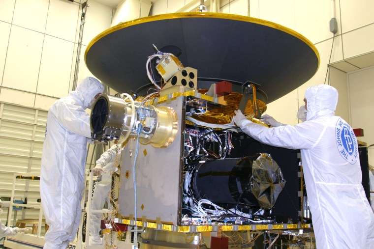 Team members at the Johns Hopkins University Applied Physics Laboratory attach New Horizons' high-gain antenna assembly during processing in April 2005. The spacecraft is carrying a compact disc with 435,000 digitized names recorded on it.