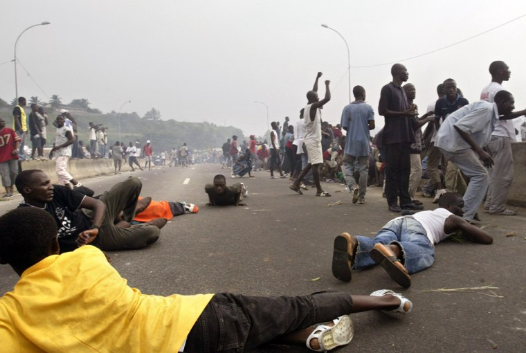 Supporters of Ivorian President Gbagbo run for cover in Abidjan