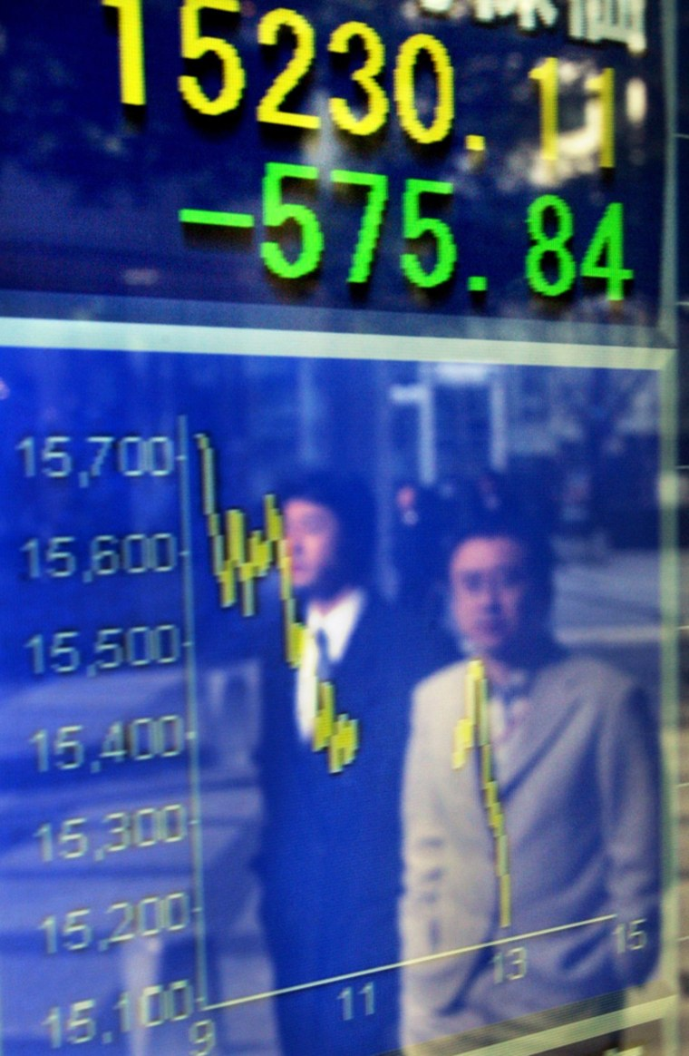 Businessmen look at the drop in stocks lit up outside a brokerage in Tokyo