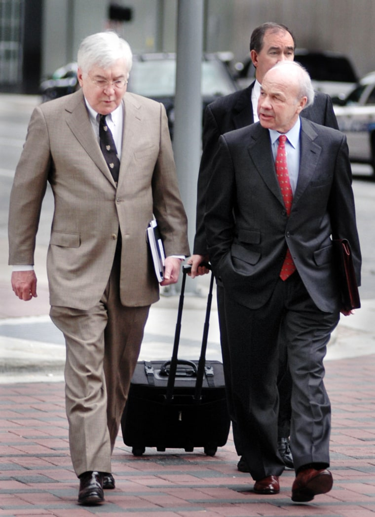 Former CEO of Enron, Kenneth Lay, talks to his attorney Mike Ramsey while on their way to the Houston Federal Courthouse