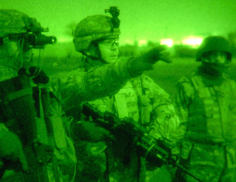 US Army officer Maj. Engen gestures beside Capt. Fournier and an Iraqi army officer during a raid in Baiji