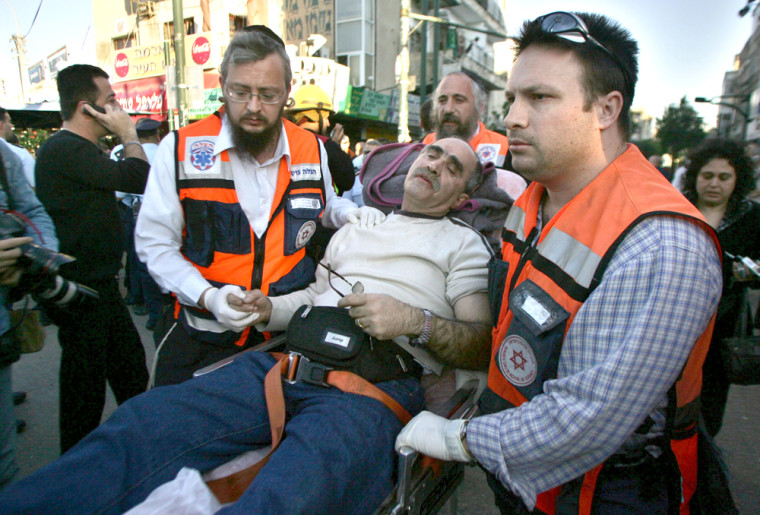 Israeli paramedics wheel an injured man on a stretcher at the site of a suicide bombing in Tel Aviv on Thursday.