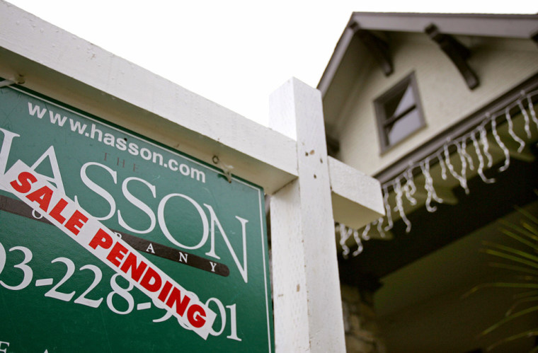 A realtor's sign hangs in front of a house for sale in Portland