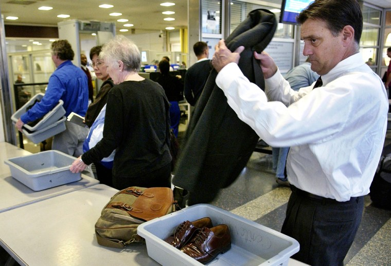 A passenger removes his coat as he passes through security screening at Reagan National Airport near Washington